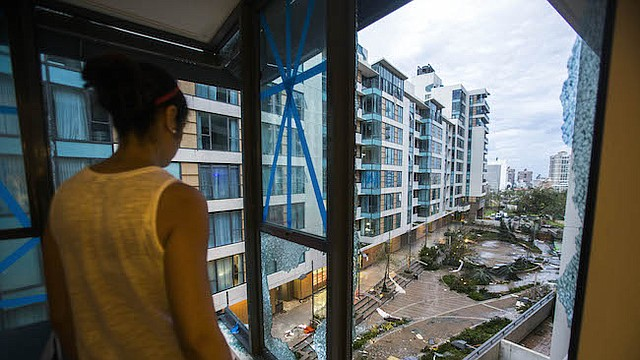 El dueño de un apartamento dañado mira las ventanas rotas de su apartamento en el complejo Ciudadela de Santurce en San Juan, Puerto Rico.