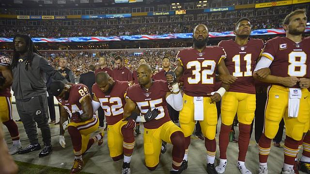 Jugadores de Redskins durante el himno nacional la noche del domingo en el campo de Fedex en Landover, Maryland.