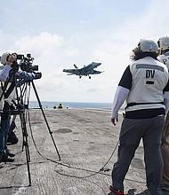 """Los anfitriones Beth Wilson y Marty Kelsey, a la derecha, filman un episodio de """"STEM en 30"""" a bordo del portaaviones Dwight D. Eisenhower. La transmisión por Internet se transmitirá el 18 de octubre."""