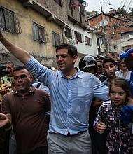 Carlos Ocariz, candidato a gobernador del estado de Miranda (centro) saluda a los partidarios mientras se dirige a una mesa de votación reubicada antes de las elecciones de gobernadores estatales en Caracas, Venezuela, el 15 de octubre de 2017.