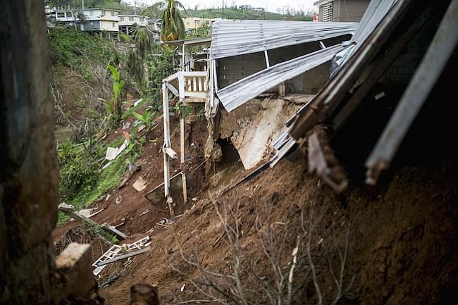 Un derrumbe de las inundaciones del huracán María se ve en la parte posterior de una casa dañada en Barranquitas, Puerto Rico, el 18 de octubre de 2017.