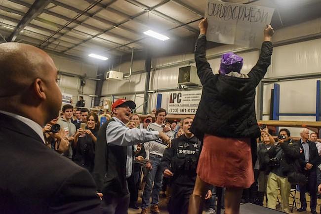 Un protestantes toma el escenario luego de que el Senador Marco Rubio, Republicano por Florida, presenta al candidato a gobernador de Virginia, Ed Gillespie, el lunes en Sterling, Va. Afuera de la manifestación, activistas de los derechos de inmigrantes llamaron racista a Gillespie por una publicidad de la campaña que dicen que coloca a los inmigrantes como chivos expiatorios.