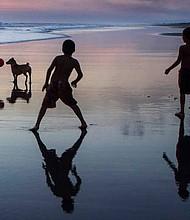 Niños se divierten jugando en la orilla de la playa al atardecer.