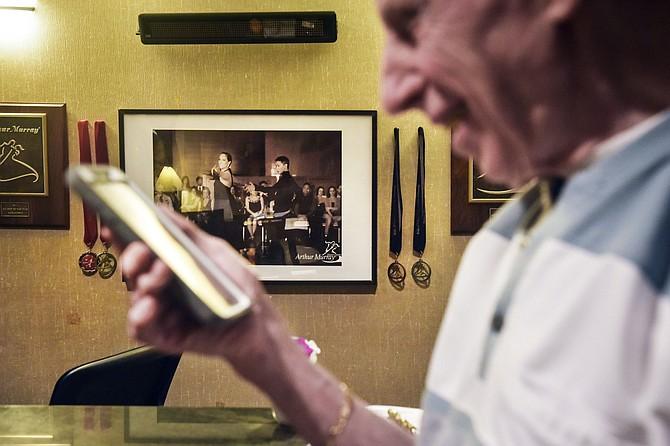 El coronel retirado de la Fuerza Aérea Charlie Heimach recibe una llamada telefónica de Galtsog Gantulga (en la foto de fondo) durante la detención de Gantulga por el Servicio de Inmigración y Aduanas de Estados Unidos en agosto.