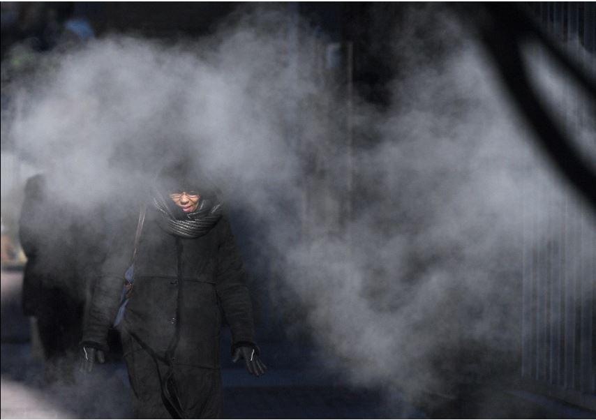 Un peatón camina a través del vapor a lo largo de la calle 10 del noroeste de Washington.