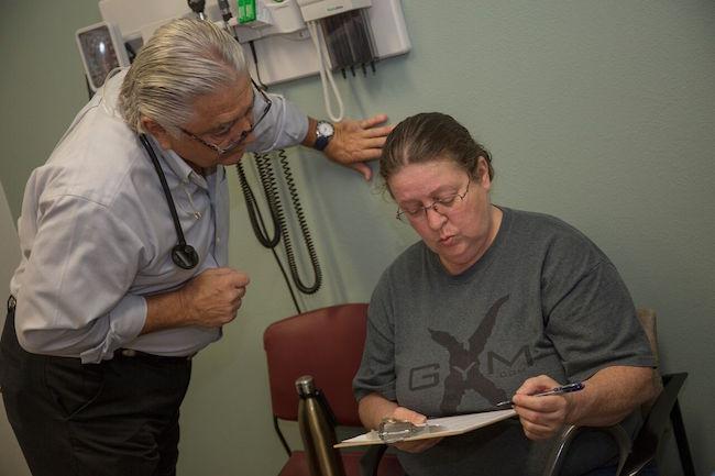El doctor Ronald Cirillo ayuda a Deborah Hatfield a llenar formularios en la clínica de Florida Turning Points, antes de hacerle la prueba para saber si tiene hepatitis C.