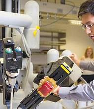 SAN DIEGO.- Estudiosos de Laboratorio del área de Robótica y Controles Avanzados de UC San Diego trabajan en la investigación y desarrollo de enfoques innovadores sobre el empleo de la robótica para asistir a veteranos heridos a mantener una vida más activa y la mejor calidad de la misma, que sea posible. En la gráfica Michael Yip, director de Laboratorio, trabaja en la Marina de los Estados Unidos para crear Ortesis y Prótesis robóticas que se ajusten a las actividades del usuario. Foto-Cortesía: UCSD.