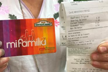 Rebeca González sostiene una copia de su recibo y su tarjeta de lealtad del mercado Northgate. La tarjeta registra los gastos de González en productos frescos y sanos, para luego darle su recompensa en forma de más dólares para comprar productos saludables.