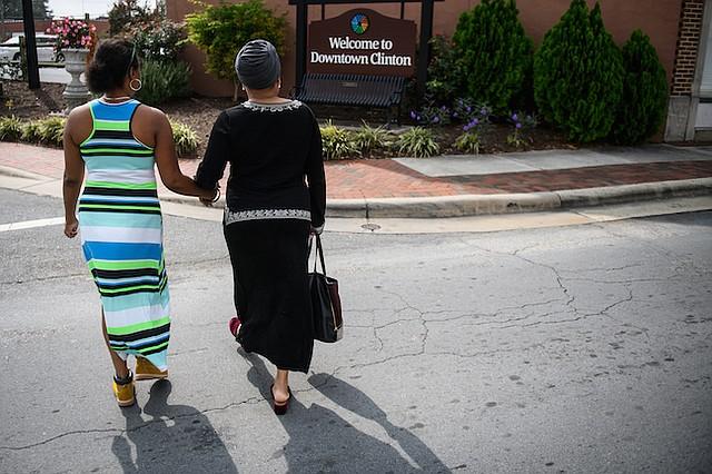 Jean Moore (derecha) sostiene la mano de su hermana, Ruby Wilson, mientras cruzan una calle el 12 de octubre de 2017 en Clinton, Carolina del Norte