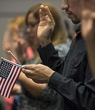 CIUDADANOS. Un postulante a la ciudadanía estadounidense sostiene una bandera de EE.UU. mientras toma el Juramento de Lealtad en una ceremonia de naturalización.