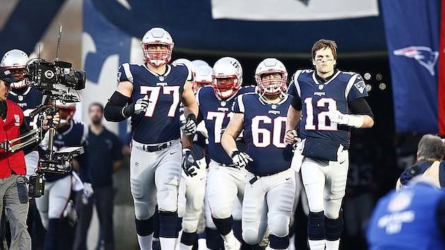 DINASTÍA. El mariscal de campo de New England, Tom Brady (der.), salta al terreno del Gillete Stadium con sus compañeros antes del partido por el campeonato de la AFC el 21 de enero.