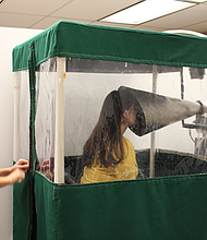 """La asistente de pregrado Shira Rubin muestra cómo funciona la """"Máquina Gesundheit"""", que recoge muestras de virus de la respiración que exhalan estudiantes enfermos. Rubin ayuda a la doctora Somayeh Youssefi (izq.) a preparar la máquina, antes que la utilicen los pacientes."""