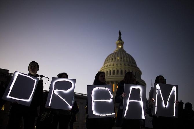 Manifestantes sostienen letreros luminosos durante una protesta en apoyo a DACA fuera del edificio del Capitolio, en Washington el 18 de enero de 2018.