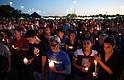 La gente se reúne para una vigilia a la luz de las velas el jueves en honor a las víctimas del tiroteo de la escuela secundaria Marjory Stoneman Douglas en Parkland, Florida.
