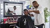 Corey Thomas le corta el pelo a un cliente en la barbería A New You, en Inglewood, California, el 9 de marzo de 2018.