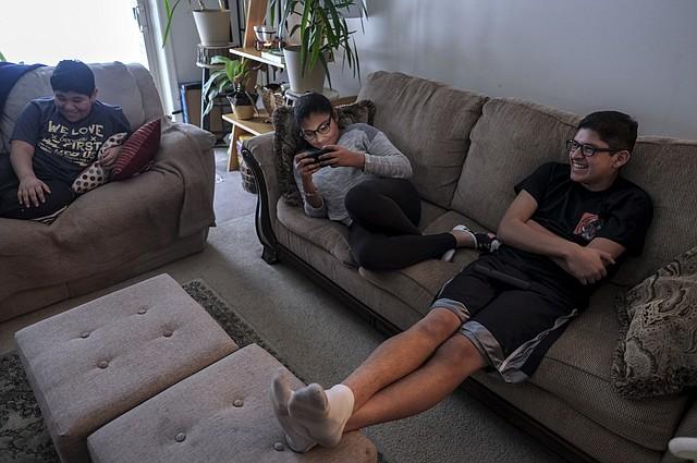 Los hermanos Martínez, Emilio, de 11, Miranda, de 12 y Adolfo, de 16, a la derecha, ven un programa de comedias en la televisión en su casa en Owings Mills, Maryland.