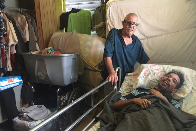 Osvaldo Martínez (izq.) cuida a su hijo, Osvaldo Daniel Martínez, quien sufre una discapacidad progresiva y tiene Medicaid. Con pocos neurólogos en la isla, el joven todavía no ha podido ver a un especialista para tener un diagnóstico oficial.