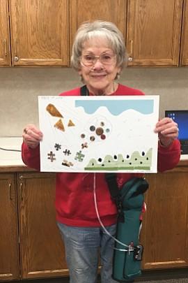 Joan Cousins, quien fue diagnosticada con EPOC hace dos décadas, sostiene un collage que ella misma hizo con piezas de un rompecabezas y botones. Fumó durante 46 años antes de dejar el hábito.