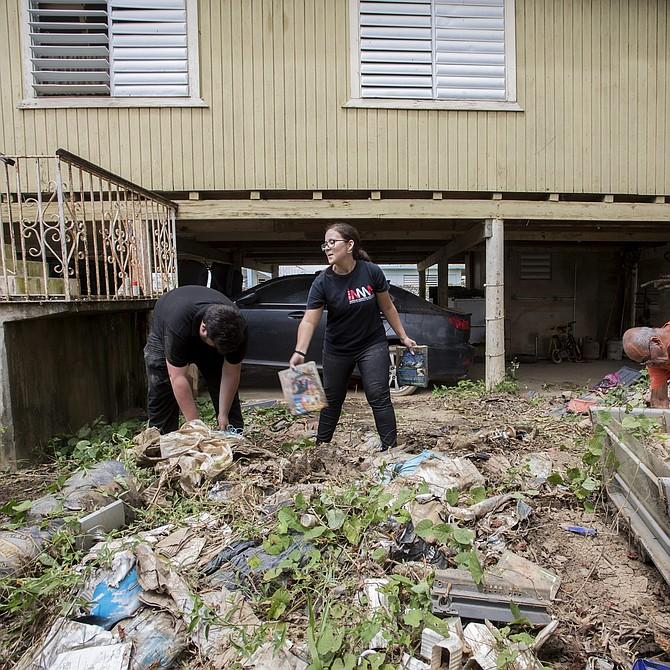 El hombre con camisa naranja está ayudando a limpiar la casa de su hermano. Voluntarios de Mentes Puertorriqueñas en Acción (camisa azul) participan en la labor.