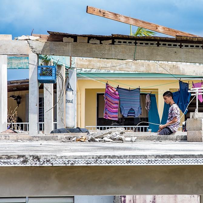 Las casas sin techo son algo común al punto que se ha vuelto normal en muchas áreas de Puerto Rico. Aquí un niño está expuesto en esta estructura que perdió el techo.