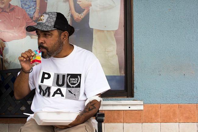 García toma un jugo fuera del Fresenius Kidney Care en Humacao, Puerto Rico, después de recibir diálisis. Su comida, que provee Renal Council, una organización local sin fines de lucro, incluye arroz, carne roja y vegetales.