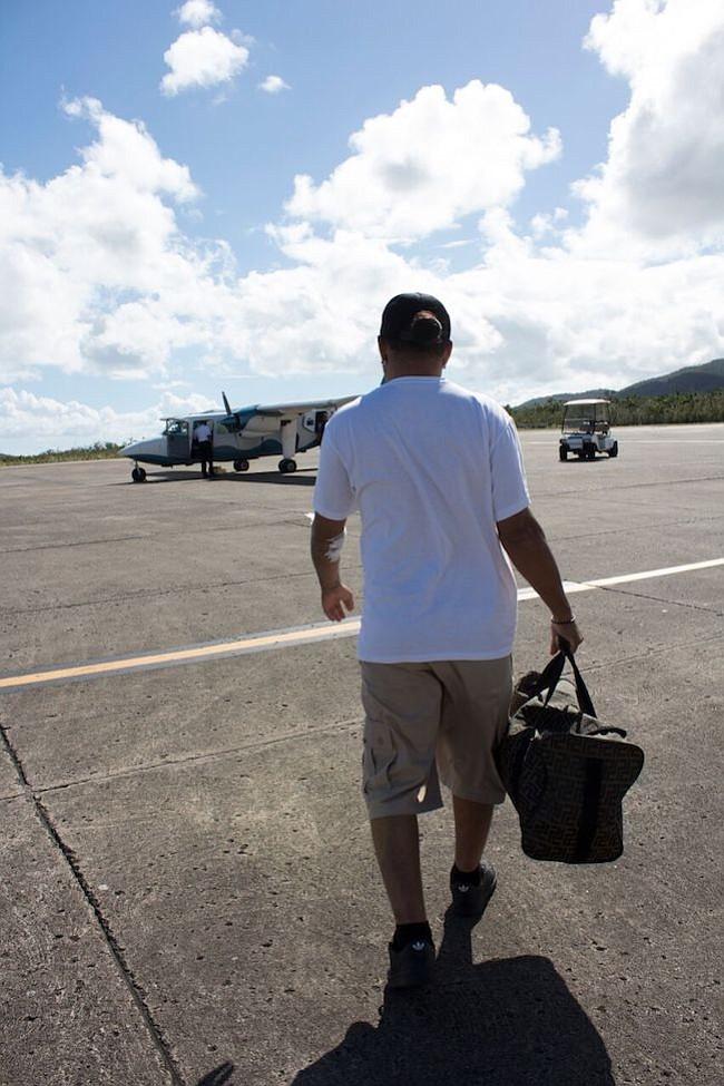 Joe García camina por la pista para tomar el avión que lo llevará a Vieques. Lleva vendas en su brazo porque acaba de terminar su diálisis.