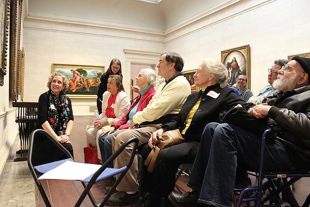 Lorena Bradford (izq.), de la National Gallery of Art, en Washington, D.C., lidera una sesión del programa Just Us, el 5 de marzo, con un grupo de pacientes de Alzheimer y sus cuidadores. El programa genera discusiones sobre obras de arte.