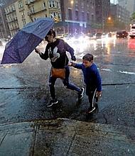LLUVIAS. Una mujer cruza la calle con un niño durante una tormenta en Nueva York
