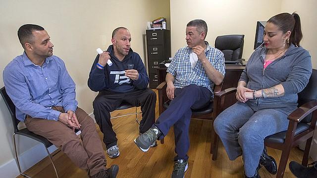 De izq. a der., Felito Díaz, Julio César Santiago, Richard López e Irma Bermúdez charlan en Casa Esperanza, un complejo que ofrece tratamientos, programas de residencia y vivienda temporal en Roxbury, Boston.