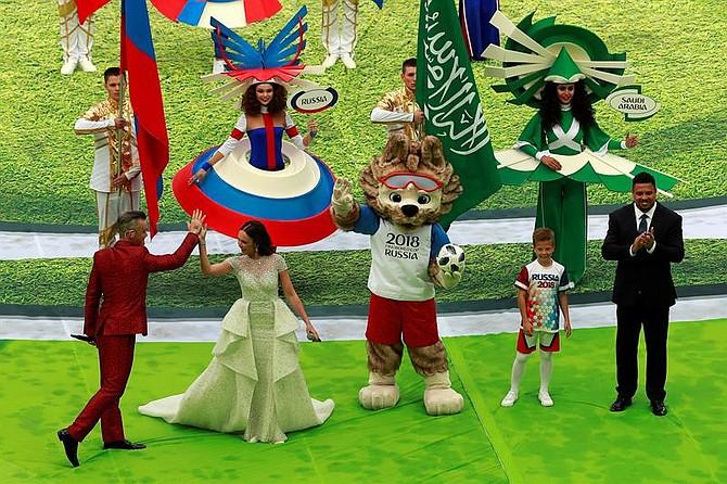 El cantante de pop británico Robbie Williams (i) y la soprano rusa Aída Garifullina, junto con el ex futbolista brasileño Ronaldo Nazário