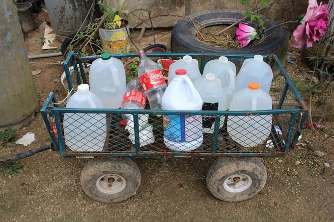 Elba Negrón Carreras utiliza botellas de plástico y leche para cargar agua. Ella y sus dos hijos deben caminar media hora hasta una estación para llevar a casa agua potable para cocinar, beber y hasta para ducharse.