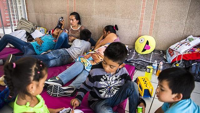 ASILO. Miembros de las familias Romero y Arcos esperan para pedir asilo en los Estados Unidos en el Puerto de Entrada Nogales en el lado de México de la frontera.