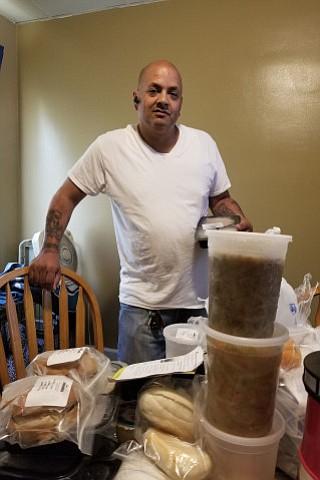 Feliciano Pagan, beneficiario de Medicaid en Philadelphia, junto a sus comidas médicamente diseñadas preparadas por la organización sin fines de lucro MANNA y pagadas por Health Partners Plans, su plan de salud de Medicaid.