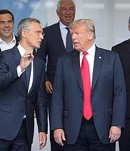 CUMBRE. El secretario general de la OTAN, Jens Stoltenberg (izda), conversa con el presidente Donald Trump durante la foto de familia de la cumbre de jefes de estado de la OTAN en Bruselas, Bélgica, el 11 de julio de 2018