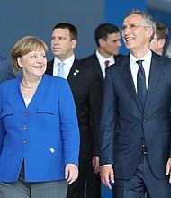 CUMBRE. El secretario general de la OTAN, Jens Stoltenberg conversa con la canciller alemana Angela Merkel, durante la foto de familia de la cumbre de jefes de estado de la OTAN que se celebra en Bruselas, Bélgica