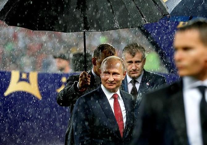 Putin con paraguas y sus invitados mojados, otra foto viral del Mundial