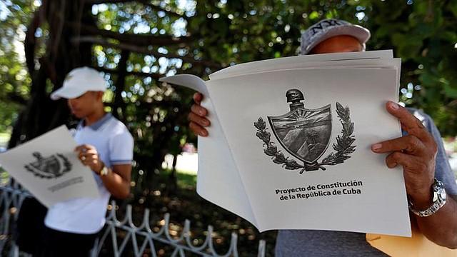 LEYES. Dos personas leen el Proyecto de Constitución de la República de Cuba