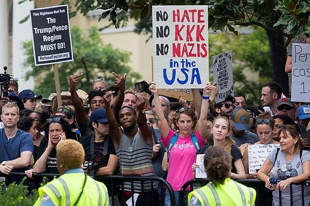 EE.UU. Contramanifestantes detrás de una línea policial señalando a los supremacistas blancos durante el mitin de Unite the Right en Lafayette Park en Washington, DC.