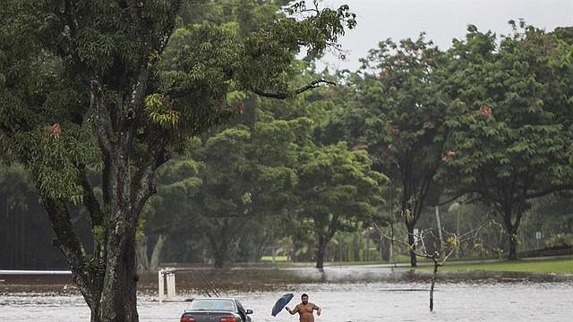 CLIMA. El propietario de un coche, prácticamente sumergido, intenta rescatar objetos personales de su interior, en una avenida afectada por las inundaciones provocadas por el paso del huracán Lane en Hilo, Hawái, el 23 de agosto de 2018
