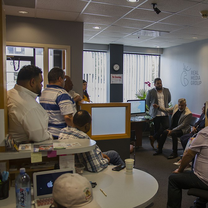Luis Morales (sentado), comparte con los asistentes su visión para la Super 1300 AM y la 100.1 FM que será la primera y única estación latina en Boston.