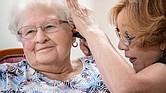 Janie York examina el oído de Elaine Martin en SilverRidge Assisted Living, en Gretna, Nebraska, en agosto. Martin tenía bastante cera en sus oídos, antes que York le realizara una limpieza y comenzara a usar audífonos. Ahora, York le limpia los oídos a Martin con regularidad.