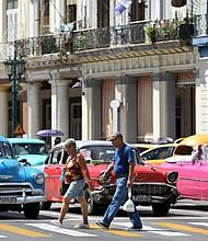 CUBA. Un hombre y una mujer caminan frente a automóviles antiguos en La Habana