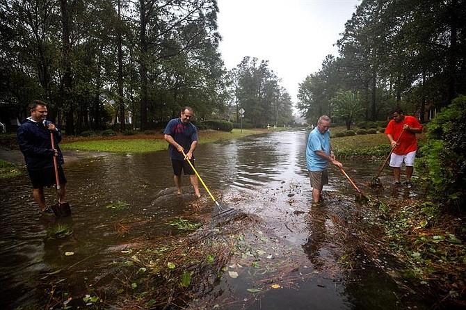 CLIMA. Varios vecinos intentan limpiar una calle inundada tras el paso del huracán Florence, en Wilmington, Carolina del Norte, el 14 de septiembre del 2018