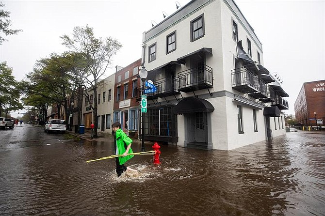 Vecinos caminan por una calle inundada tras el paso del huracán Florence, en Wilmington