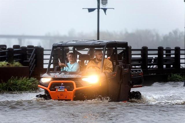 CLIMA. Dos vecinos circulan por una calle inundada tras el paso del huracán Florence, en Wilmington, Carolina del Norte, EE.UU.