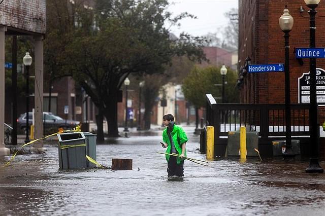 CLIMA. Varios vecinos caminan por una calle inundada tras el paso del huracán Florence, en Wilmington, Carolina del Norte