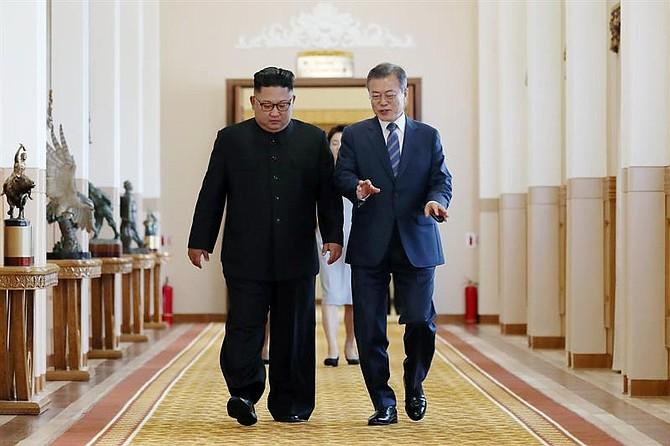 CUMBRE. El presidente surcoreano, Moon Jae-in (d), y el líder norcoreano, Kim Jong-un (i), conversan antes de una reunión en Pionyang, Corea del Norte, el 19 de septiembre de 2018
