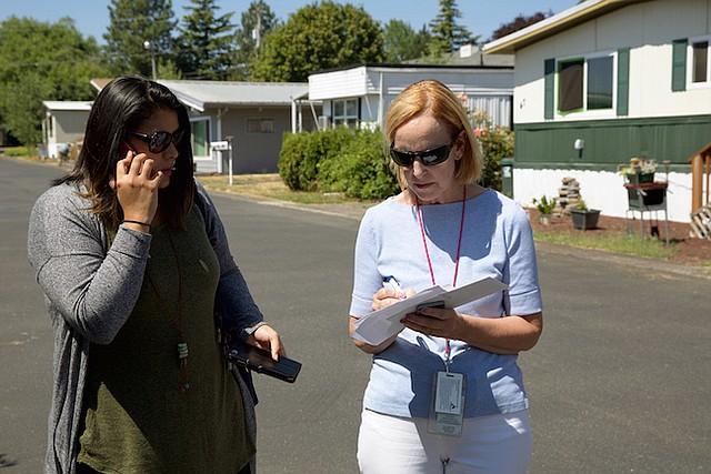 Mary Horman (derecha), enfermera certificada del condado de Clackamas, en Oregon, y Liz Baca, especialista en intervención de enfermedades del condado, buscan la dirección de una de las personas que deben visitar como parte de su trabajo. Ellas visitan a parejas sexuales de personas diagnosticadas con enfermedades de trasmisión sexual, para que se hagan pruebas y eventualmente reciban tratamiento.