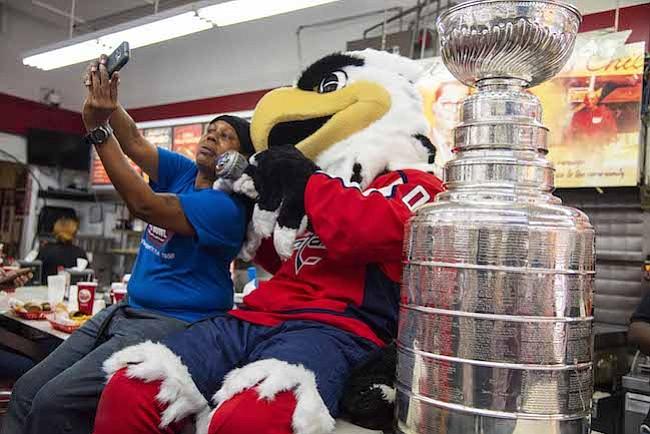 TROFEO. Una fan de los Washington Capitals se toma una selfie con la Stanley Cup y la mascota Slapshot durante una gira del trofeo en Ben's Chili Bowl antes del primer partido de la temporada el miércoles por la noche en Washington, DC.