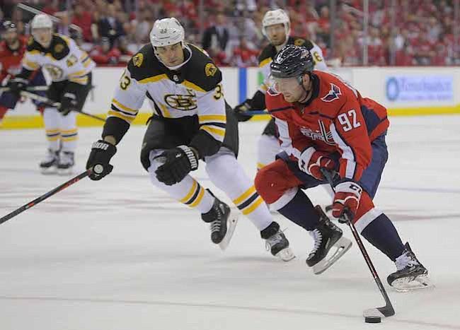 TRIUNFO. El centro de los Capitals Evgeny Kuznetsov (92) avanza hacia la red contra el defensa Zueno Chara (33) de los Bruins, durante el primer juego de la franquicia capitalina en la temporada NHL. Kuznetsov tuvo dos goles cuando Washington derrotó a Boston, 7-0, el miércoles por la noche.
